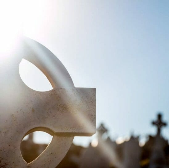 A Celtic Cross in a Graveyard with the Sun Shining on it