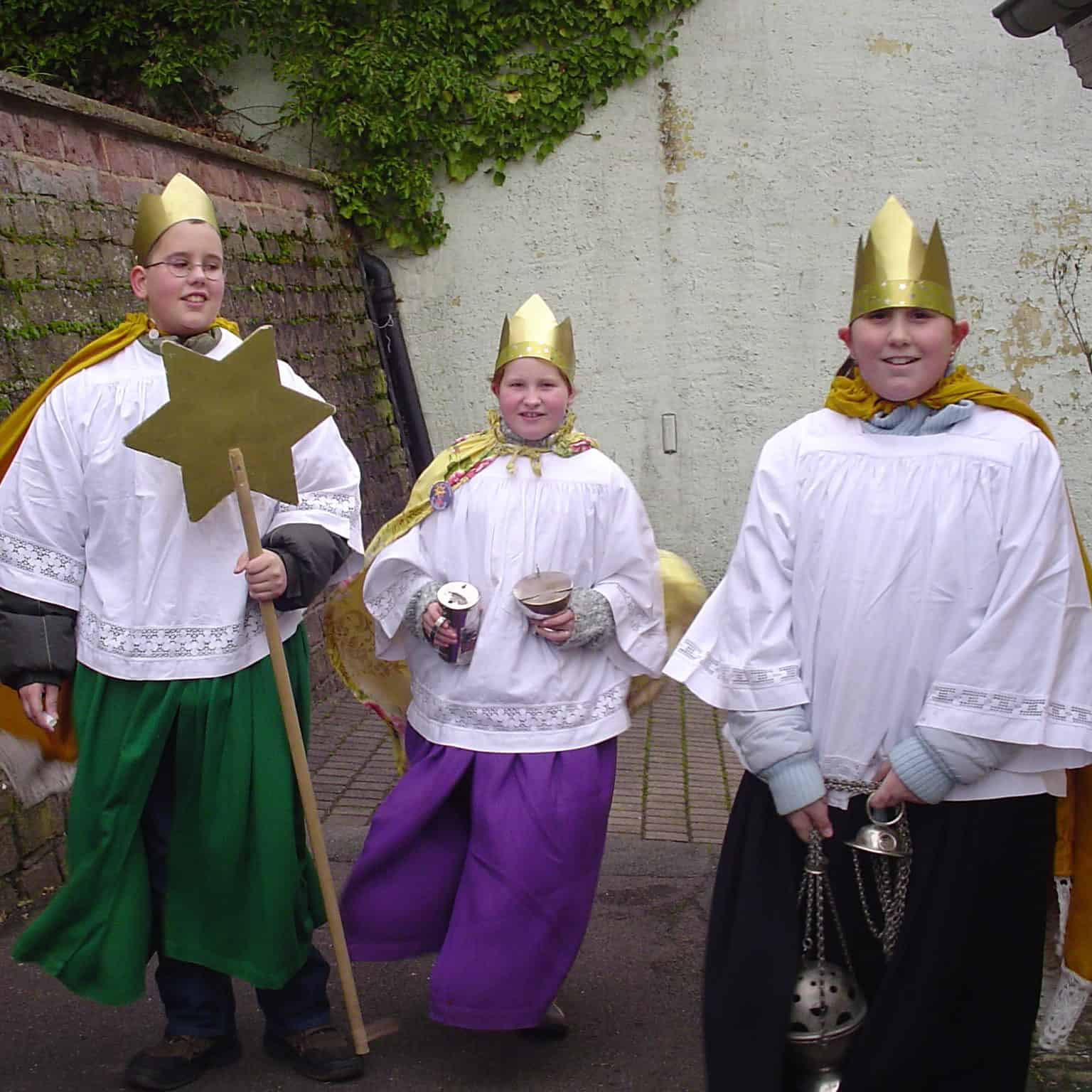 three children in colorful robes, white shirts, and gold crowns in a play of the three kinds for Epiphany